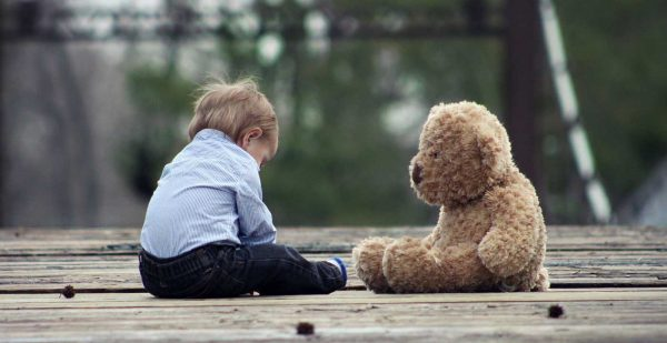 Young Boy Sitting With Large Teddy Bear