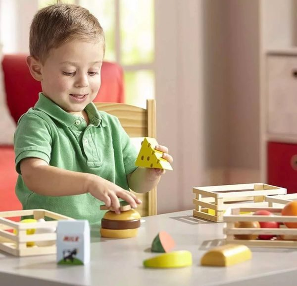 Boy Playing With Wooden Food Toys